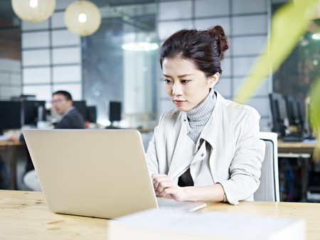 business woman working: young asian business woman working in office using laptop computer. Stock Photo