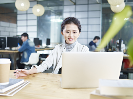 young asian business woman working in office using laptop computer. Stock Photo