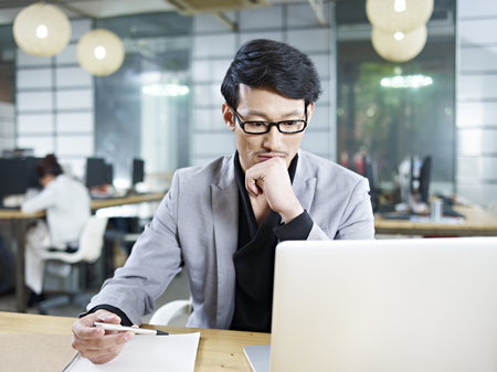 asian business man: young asian business man working in office using laptop computer.