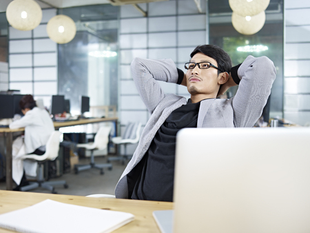 businessman thinking: young asian business executive leaning back in a chair and thinking. Stock Photo