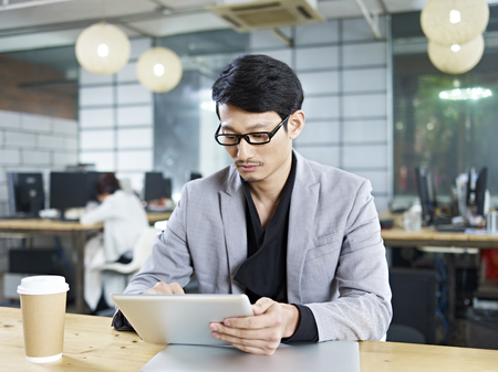 asian business man: young asian business man working in office using tablet computer.