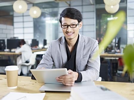 태블릿 컴퓨터를 사용하는 사무실에서 작업 젊은 아시아 비즈니스 사람.