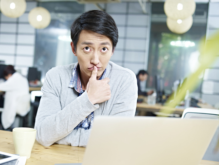 businessman thinking: young asian business person sitting at desk thinking hard.