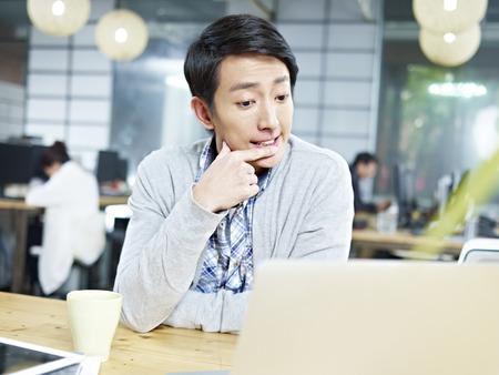 personas pensando: joven hombre de negocios asiático sentado en el escritorio pensando mucho. Foto de archivo