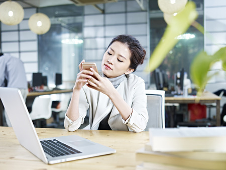 tweeting: young asian business executive sitting at desk in office playing with mobile phone.