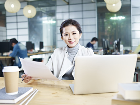founder: young asian business woman sitting at desk in office holding document looking at camera.