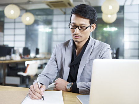 life plan: asian business man sitting at desk in office writing on a piece of paper.