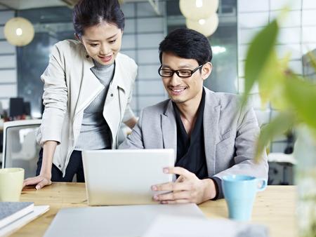 Jeunes gens d'affaires asiatiques assis au bureau travaillant ensemble à l'aide d'un ordinateur portable.