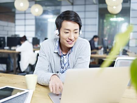 joven hombre de negocios asiático sentado en el escritorio en la oficina de trabajo con ordenador portátil mientras se escucha música con auriculares. Foto de archivo