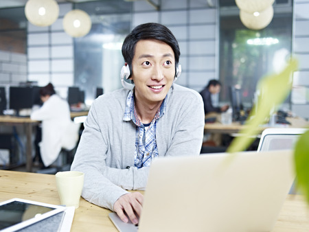 happy worker: young asian businessman sitting at desk in office working using laptop computer while listening to music with headphone. Stock Photo