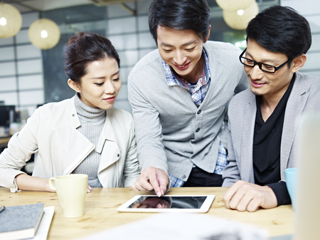 a team of young asian entrepreneurs working in office using tablet computer.