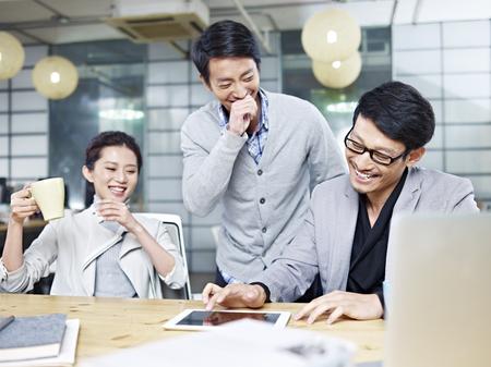 若いアジアの起業家のオフィスで働いている間楽しい時を過すのチーム。 写真素材