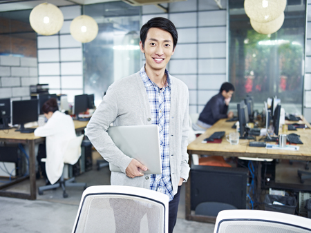 founder: confident young asian entrepreneur standing in own company with laptop computer looking at camera smiling. Stock Photo