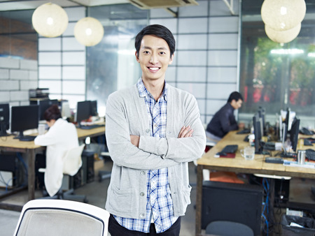 founder: confident young asian entrepreneur standing in own company looking at camera arms crossed smiling.