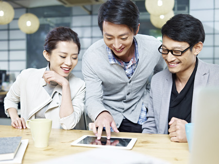 singaporean: a team of young asian entrepreneurs discussing business in office using tablet computer.