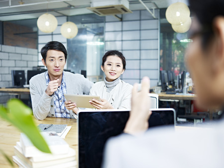 place of work: young asian business people talking chatting in office.