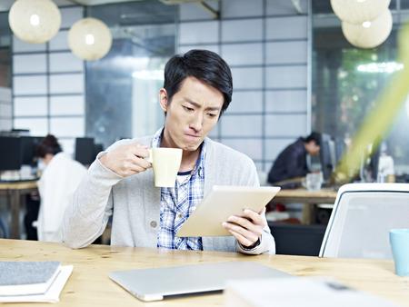usando computadora: joven asiática de la persona de negocios que mira la tablilla mientras que el consumo de café en la oficina con la expresión facial seria. Foto de archivo