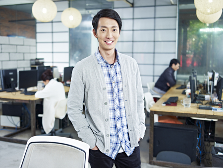 casual wear: confident young asian entrepreneur standing in own company looking at camera hands in pockets smiling.