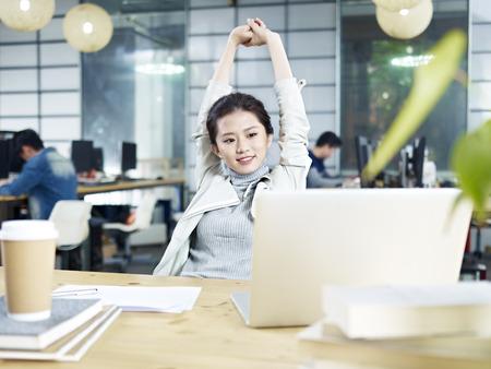 Jonge Aziatische zakenvrouw strekt overlichaam in kantoor na taak afgerond.