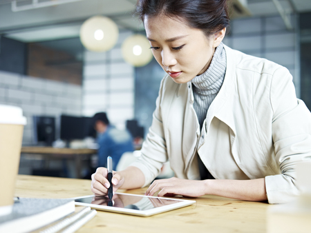 designer: young asian designer working in studio using digital drawing pen and tablet. Stock Photo