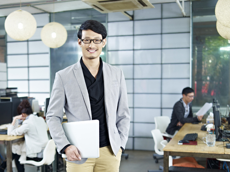 young asian entrepreneur standing in office with laptop computer under arm. Banque d'images