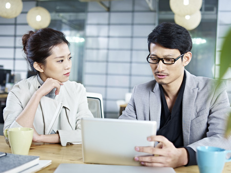 new business problems: two young asian corporate people discussing business in office using tablet computer.