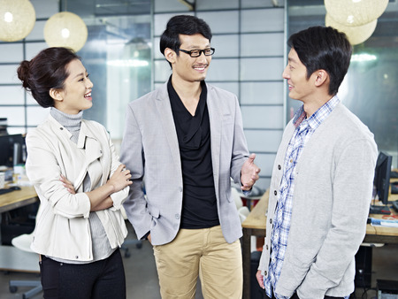 men talking: three young asian business people standing in office chatting.