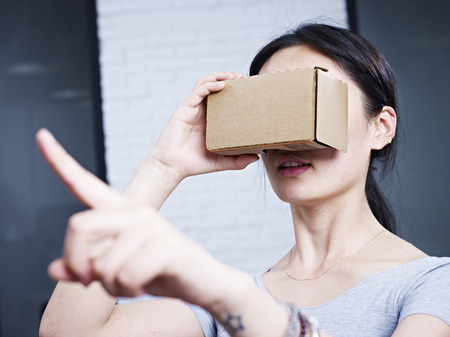 experiencing: young asian woman experiencing virtual reality with cardboard VR glasses.