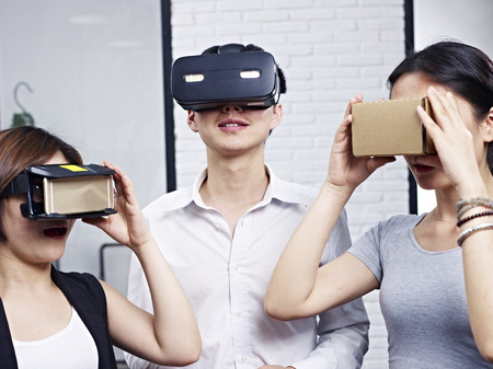 mobile headsets: three young asian people wearing different types of virtual reality (VR) goggles. Stock Photo
