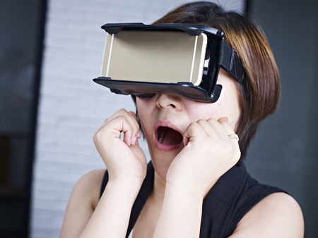 experiencing: young asian woman experiencing virtual reality with head-mounted VR goggles. Stock Photo