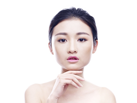 beauty shot: studio portrait of a young asian woman, looking at camera, hand on chin, frontal view, isolated on white.