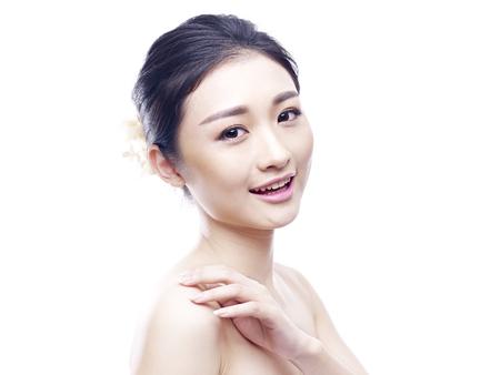 studio portret van een jonge Aziatische vrouw, kijkend naar de camera, glimlachen, zijaanzicht, geïsoleerd op wit.