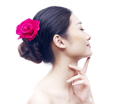 china rose: studio portrait of a young asian woman, eyes closed, side view, isolated on white. Stock Photo