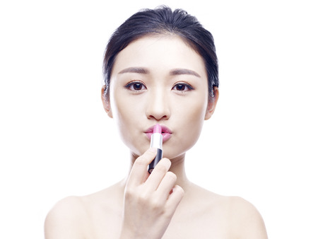 applying: young asian woman applying lipstick, isolated on white background.