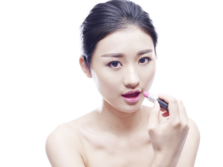 young asian woman applying lipstick, isolated on white background.