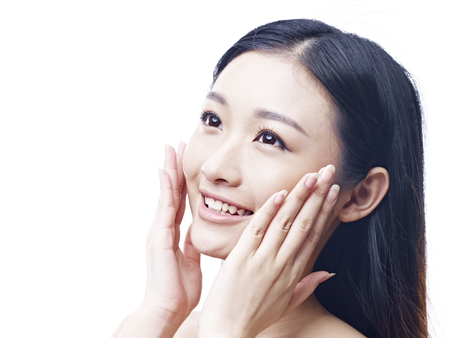 girl looking up: young asian woman rubbing face with hands, happy and smiling, isolated on white background. Stock Photo