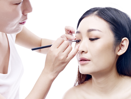 asia people: makeup artist working on a beautiful young female asian model, isolated on white background. Stock Photo