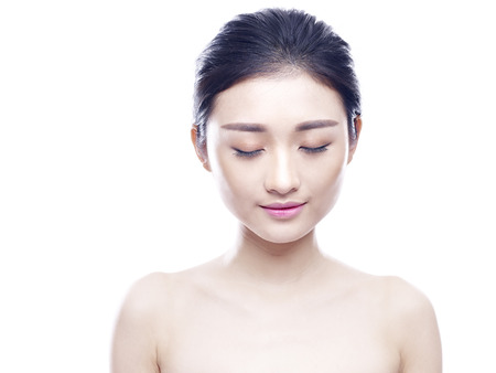 beautiful naked woman: studio portrait of a young and beautiful asian woman, eyes closed, isolated on white background.
