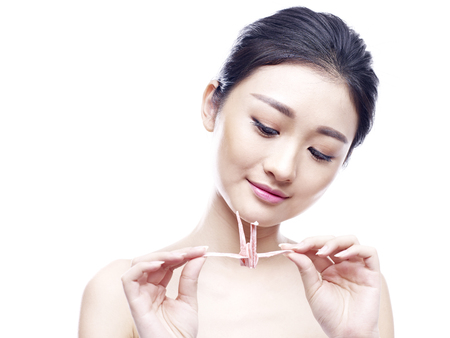 cherishing: young asian woman holding and looking at a paper crane, isolated on white background.