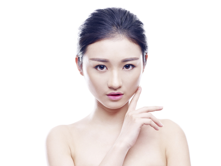 studio portrait of a young and beautiful asian woman, hand on chin, looking at camera, isolated on white background.