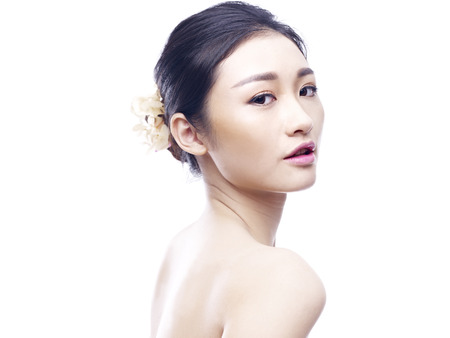 studio portrait of a young and beautiful asian woman, side view, looking at camera, isolated on white background.