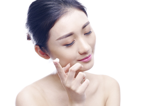 young asian woman applying lotion or cream to face, isolated on white background.