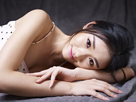 young and beautiful asian woman lying on floor, looking at camera smiling.
