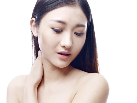 hair problem: young and beautiful asian woman, hand rubbing neck, isolated on white background. Stock Photo