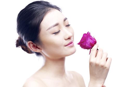 joven y bella mujer asiática disfrutando de la fragancia de una rosa roja, aislado en fondo blanco.