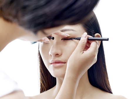 makeup artist working on eyeliner of a young asian model, isolated on white background.