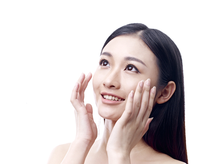young asian woman rubbing face with hands, happy and smiling, isolated on white background. Stock Photo