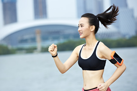 asia people: young and beautiful asian female runner running by a lake in city park.