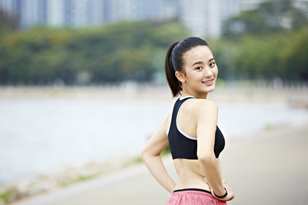 young asian woman runner turning to look at camera before running. Stock Photo