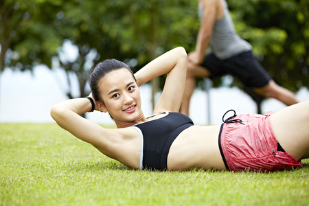 situp: young asian woman doing sit-ups on grass in city park.